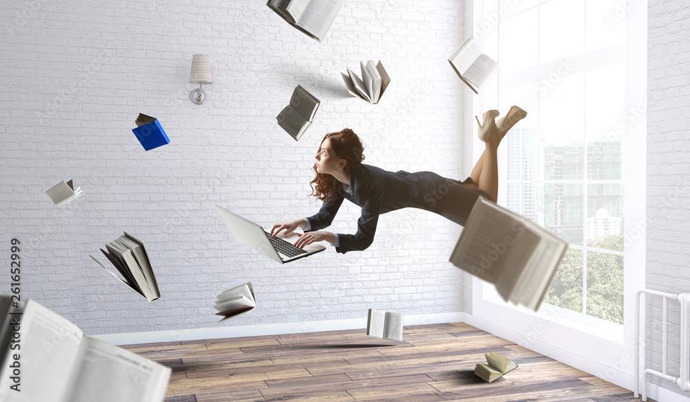 Fototapeta Joyful beautiful young levitating businesswoman. Mixed media