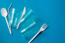 White Single-use Plastic Knife, Spoon, Fork And Plastic Drink Straws On A Blue Background. Say No To Single Use Plastic. Environmental, Pollution Concept.