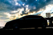 car silhouette on evening sky during the sunset b