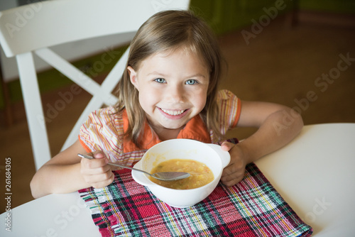 Little girl having lunch and eating soup Canvas Print