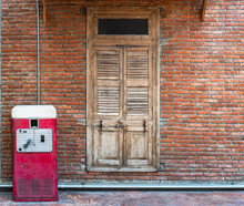 The Old Red Classic Vintage Retro Auto Vending Machine For Soft Drink Standing In Front Of The Old Brick House With Ancient Wooden Door.