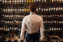 Rack With Wine Bottles And Bartender Or Cavist Man Backside On Foreground.