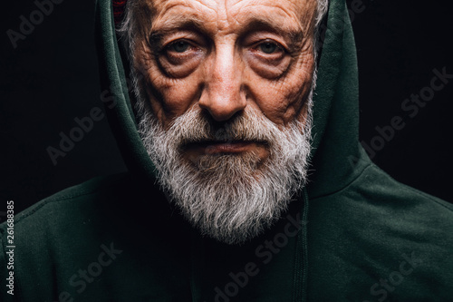 Close-up of a mature old-aged man in green hoodie with wrinkled weathered face, Canvas Print