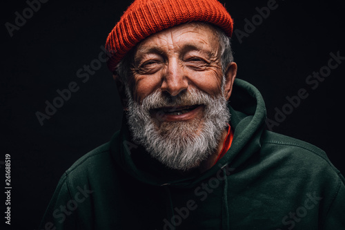 Obraz Close up portrait of happy 70-year-old optimist man with smiling wrinkled face, dressed in hipster orange hat and green hoodie, isolated over black background. Positive and cheerful at any age. - fototapety do salonu