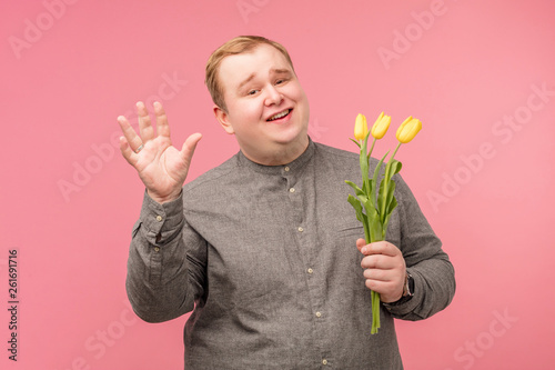 Funny cute man with bouquet of yellow flowers waits for girlfriend, going to mak Canvas Print