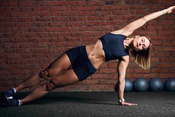 Młoda kobieta z dobrze wyszkolonym ciałem utrzymuje pozę deski bocznej podczas ćwiczeń na siłowni