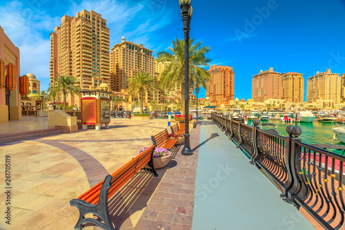Fényképezés  Benches and palm trees along marina walkway promenade in Porto Arabia at the Pearl-Qatar, Doha, with residential towers and luxury boats on background