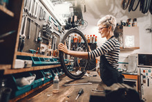 Cute Caucasian Female Worker Holding And Repairing Bicycle Wheel While Standing In Bicycle Workshop.