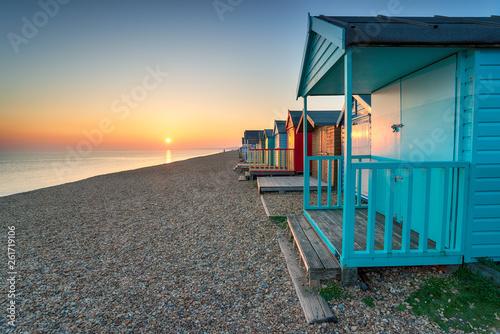 Valokuva  Stunning sunset over seaside beach huts