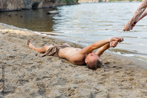 young white man in loincloth is bound by the river Wallpaper Mural
