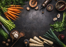 Food Background With Various Organic Farm Vegetables On Dark Rustic Table With Kitchen Utensils, Herbs And Spices, Top View. Frame. Copy Space. Vegan And Vegetarian Food Concept. Healthy Lifestyle