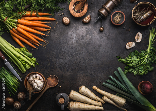 Fotografija Food background with various organic farm vegetables on dark rustic table with kitchen utensils, herbs and spices, top view