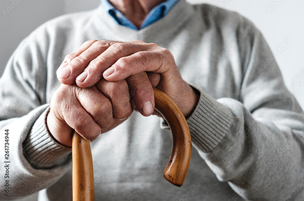 Fototapety, obrazy: Hands of an elderly man resting on a walking cane