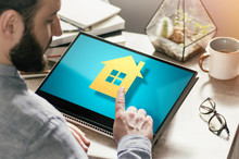 Bearded Man With Laptop At His Desk. He Presses On The House Icon. Concept Of Real Estate Buying, Booking, Advertising Via Internet. Image