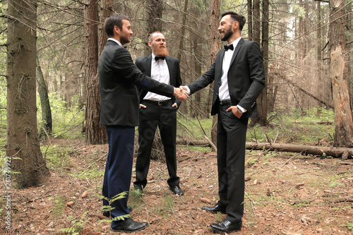 Fototapeta business partners greeting each other with handshakes at a meeting in the woods