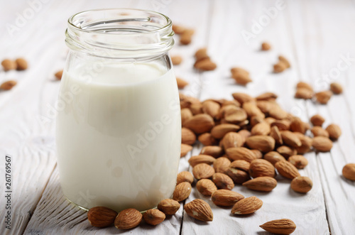 Milk or yogurt in mason jar on white wooden table with almonds aside