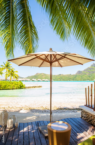 Photo  White umbrella on wooden decking with summer view of sunny beach of Bora Bora is