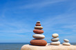 Three Zen pyramid of balanced stones on a background of the summer sea and blue sky