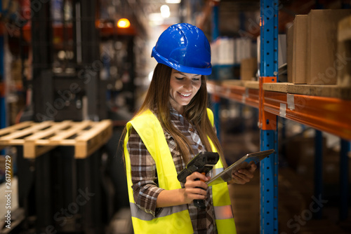 Fotografía  Smiling female worker holding tablet and bar code scanner checking inventory in distribution warehouse