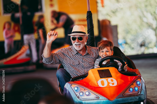 Stickers pour portes Attraction parc Grandfather and grandson having fun and spending good quality time together in amusement park. They enjoying and smiling while driving bumper car together.