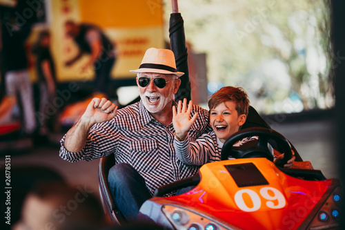 Staande foto Amusementspark Grandfather and grandson having fun and spending good quality time together in amusement park. They enjoying and smiling while driving bumper car together.