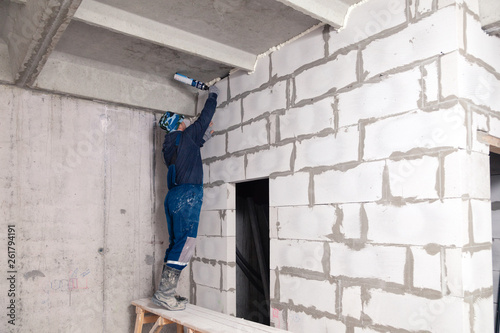 Closeup of working builder working on a wall of gray aerated concrete with rough seams with mortar and ceiling with foam Wallpaper Mural