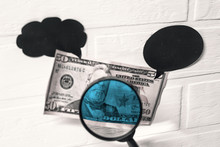 Checking Dollars For Fake. Magnifying Glass Against The Background Of A Banknote.