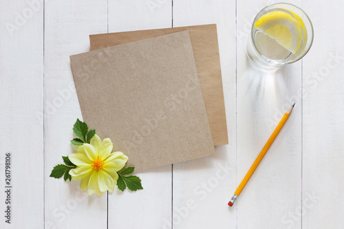Foto  Sheet of kraft paper with a pencil on wooden background