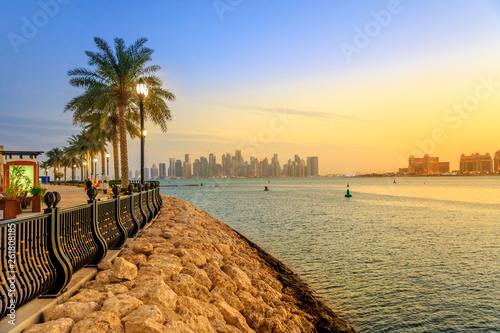 Fényképezés  Palm trees along marina walkway in Porto Arabia at the Pearl-Qatar, Doha, with skyscrapers of West Bay skyline at sunset sky