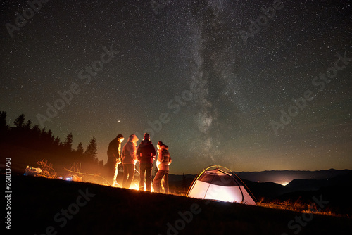 Photo sur Toile Marron chocolat Back view group of four young friends hikers having a rest together around bonfire beside camp and illuminated tourist tent at night in the mountains under starry sky full of stars and Milky way.