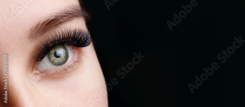 Photographie Close up view of beautiful green female eye with long eyelashes and perfect trendy eyebrows on dark background