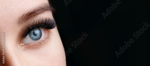 Close up view of beautiful blue female eye with long eyelashes and perfect trendy eyebrows on dark background Billede på lærred