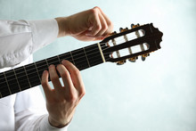 Man Tunes Classic Guitar Against Light Background, Space For Text