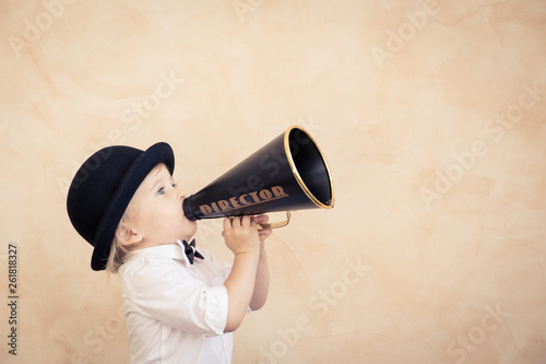 Funny child playing with black retro megaphone Wallpaper Mural