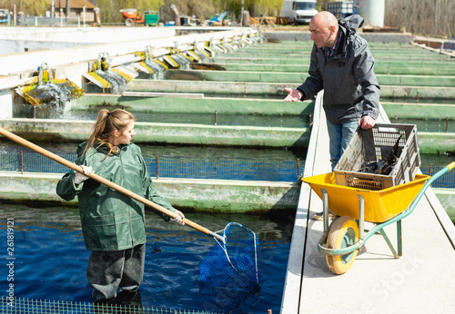 Photo Male and female fish farm workers