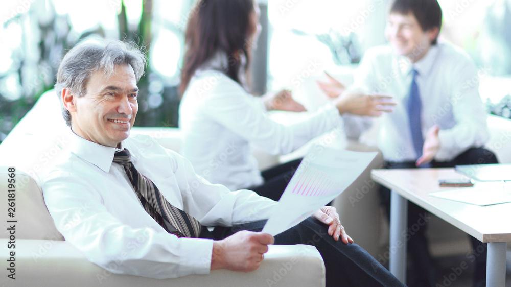 Fototapeta businessman pondering a document sitting in a modern office