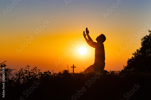 Cadres-photo bureau Rouge Silhouette of woman praying with cross in nature sunrise background, Crucifix, Symbol of Faith. Christian life crisis prayer to god.