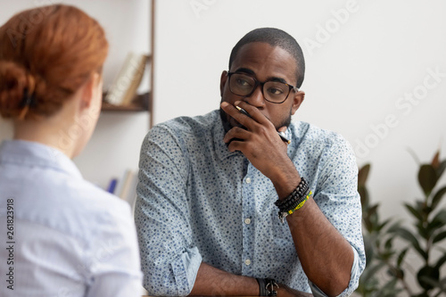 Photo Doubtful african hr talking to caucasian applicant at job interview