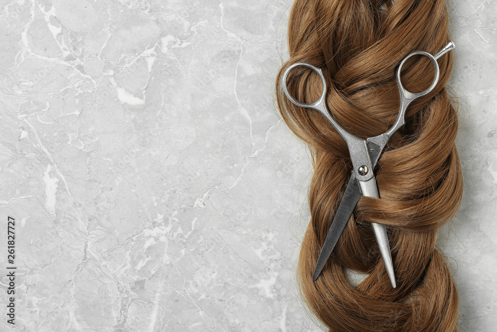 Fototapeta Flat lay composition with brown hair, scissors and space for text on grey background. Hairdresser service