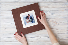 Brown Photo Book With  Leather Cover.  Stylish Wedding Photo Album. A Person Opens A Photobook. Family Photoalbum On The Table. The Womans Hand Holding A Family Photo Album