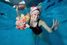 Girl Swimming Instructor Swims Underwater And Holding A Toy Pig - A Symbol Of The New Year. She Smiles And Poses For The Camera With Her Eyes Open In Santa's Hat On Her Head. Portrai