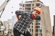 Leinwanddruck Bild - Hard work. Construction worker in protective helmet feeling back pain while working at construction site. Building construction. Pain concept