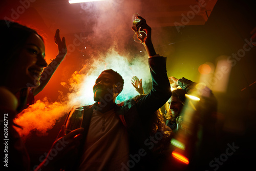 Photo Crowd of cheerful hilarious young multiethnic people drinking alcohol and dancin