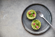 Two Tartlets On A Dark Plate In A Restaurant. Gourmet Dish.
