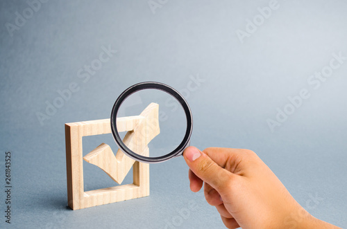 Fototapeta Magnifying glass is looking at the wooden checkmark for voting on elections on a gray background