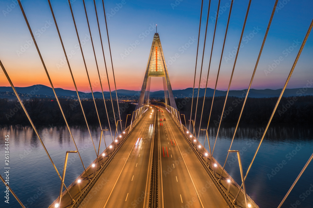 Budapest, Hungary - Aerial view of the beautiful cable-stayed Megyeri Bridge over River Danube with blue and orange sky after sunset