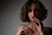 Closeup Portrait Of Magnificent Brunette Model With Curly Hair Posing In The Shadows. Empty Space