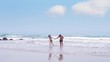 Two Asian couples walking hand in hand enjoying relax on sea beach. freedom, travel, Lifestyle and Summer Holiday Concept. Slow motion