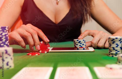 фотография  Unrecognizable woman putting poker chips on smartphone, mobile poker gambling