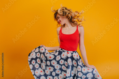 Obraz na plátně Energy girl with long curly hair in tail  listening to music with headphones on orange background in studio